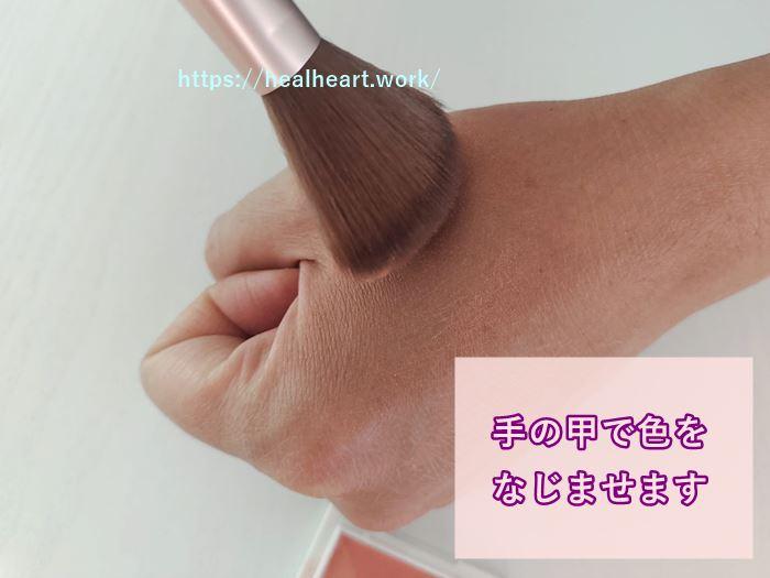 チークカラーを手の甲で馴染ませている写真